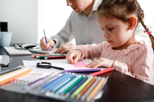 Dochter tekent met vader aan tafel