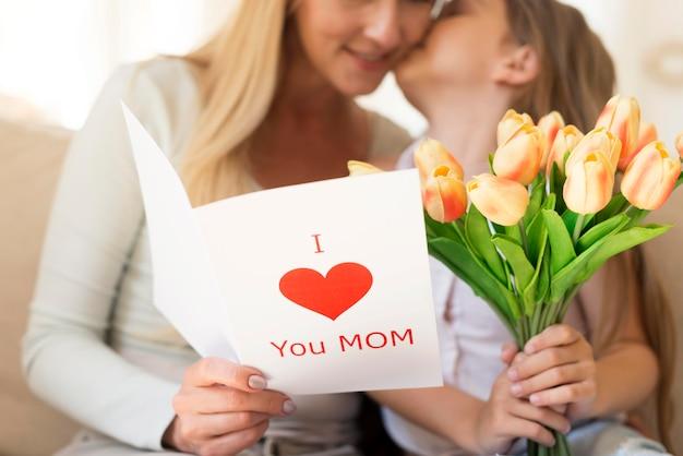 Dochter verrassende moeder met boeket bloemen en kaart