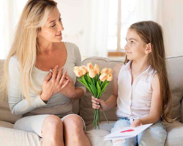 Dochter verrassende moeder met boeket bloemen