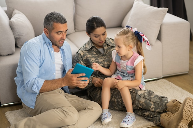 Dochter voelt zich opgewonden. dochter voelt zich opgewonden voordat ze met vader en moeder naar tekenfilm op tablet kijkt