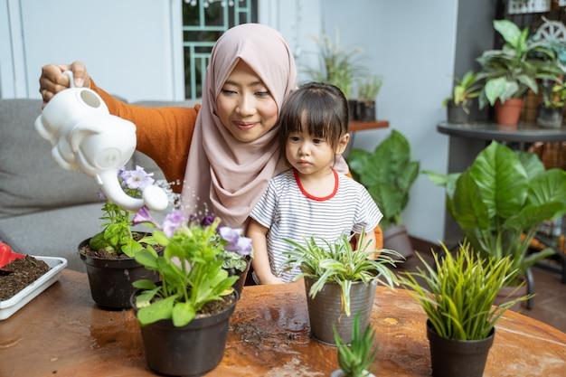 Dochter ziet haar moeder een gieter vasthouden terwijl ze planten water geeft