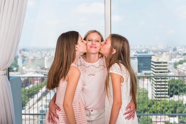 Dochters die moeder op wangen kussen