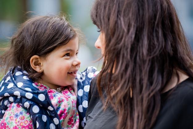 Dochtertje en moeder kijken elkaar aan en glimlachen