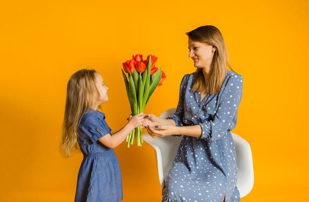 Dochtertje geeft haar moeder een boeket tulpen op een gele muur