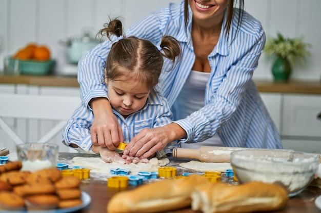 Dochtertje helpt haar moeder met het koken van koekjes tijdens de vakantie. ze rollen en snijden het deeg in de keuken.