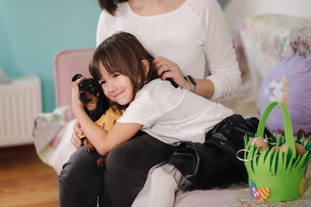 Dochtertje met moeder spelen met hond thuis en gelukkige familie pasen voorbereiden
