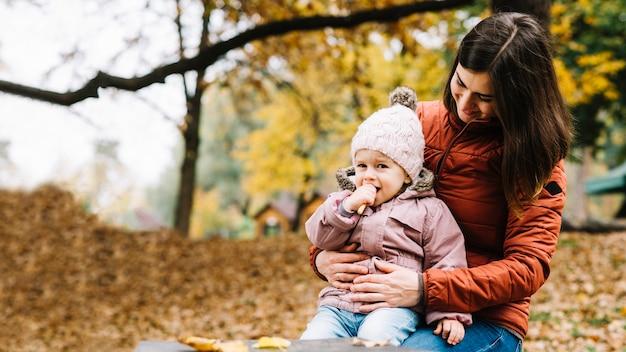 Dochterzitting op de knieën van de moeder en het eten van koekje in de herfstpark