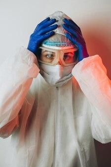 Doctor in de beschermende uniform, reperitor, bril, handschoenen aan een blauwe muur in neonlicht. een close-upportret van een arts in rood neon. een vermoeide man vecht tegen een coronavirus. covid 19