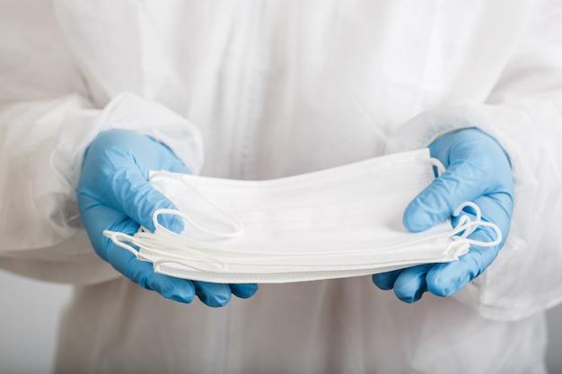 Doctor's hand met een medisch gezichtsmasker voor bescherming tegen infectie