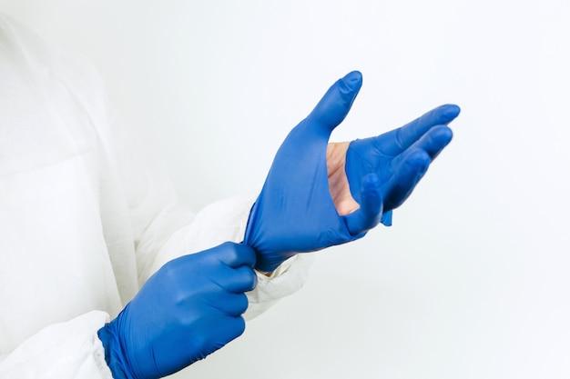 Doctor's handen close-up in gescheurde rubberen handschoenen. gescheurde medische handschoenen na een werkdag in de kliniek. artsen bestrijden de coronavirus-epidemie. covid-2019