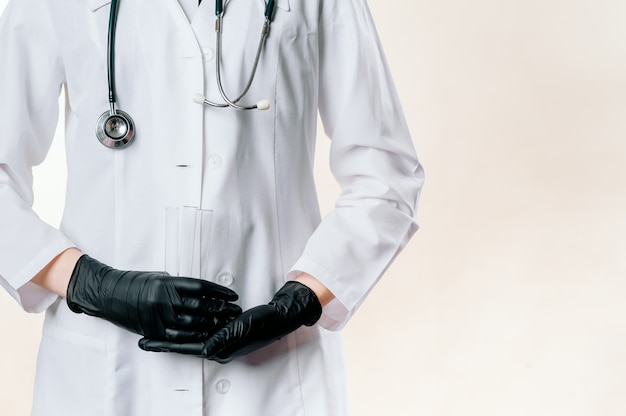 Doctor's handen in een witte jas in zwarte handschoenen houden een injectie, medicijnen op een lichte achtergrond