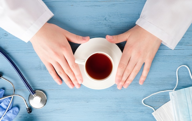 Doctor's handen met koffie aan de tafel. bureau van de dokter.