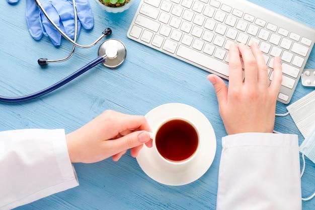 Doctor's handen met koffie en computer op een blauwe tafel