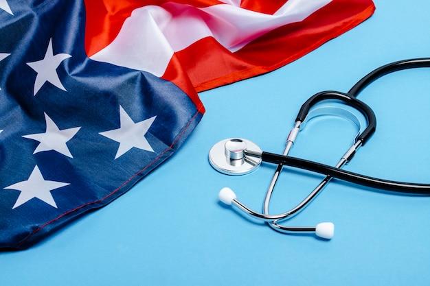 Doctor's stethoscoop en amerikaanse vlag op een blauwe ondergrond. vs geneeskundeconcept, hoog niveau, medische verzekering, beste geneeskunde, vaccin, virus, epidemie. plat lag, bovenaanzicht