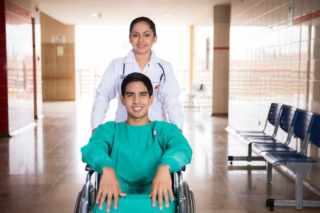 Doctora y pasiente con silla de ruedas, horizontaal.