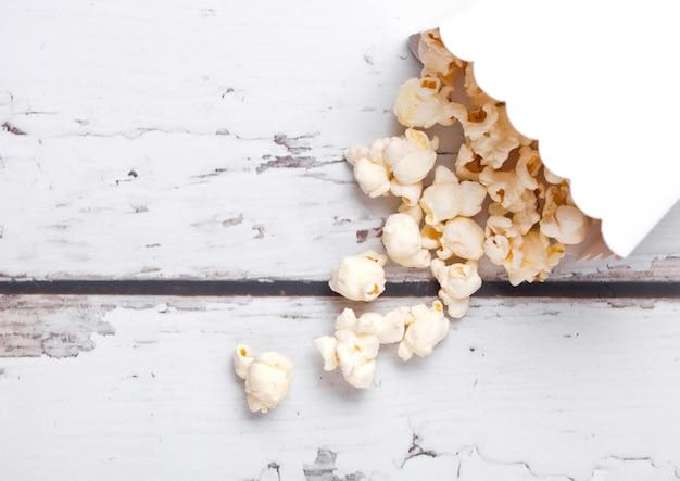 Document container met verse gezouten popcorn op houten achtergrond