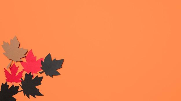 Document de herfst verlaat regeling op oranje achtergrond met exemplaarruimte