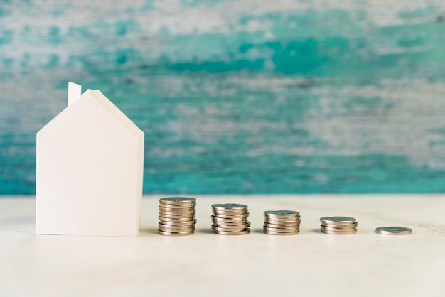 Document huismodel met stapel toenemende muntstukken op witte oppervlakte tegen doorstane muur