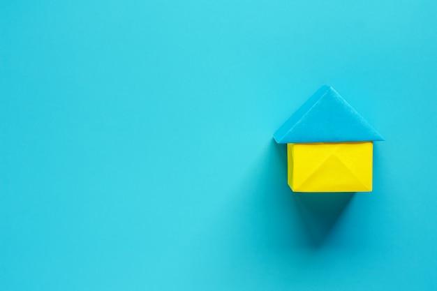Document huisorigami op blauwe achtergrond met exemplaarruimte voor huisvesting en bezitsconcept