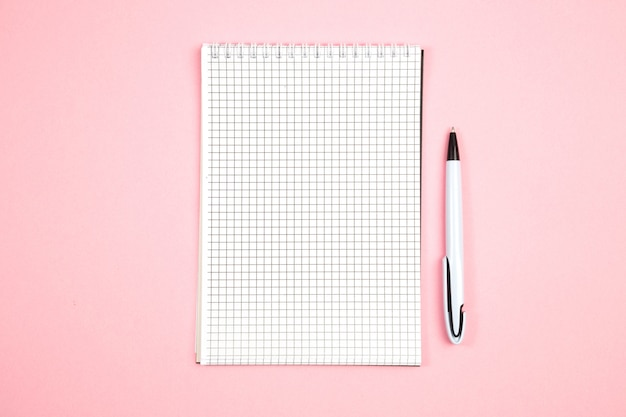 Document notitieboekje met pen op roze geïsoleerde achtergrond. bovenaanzicht. plat leggen. mockup