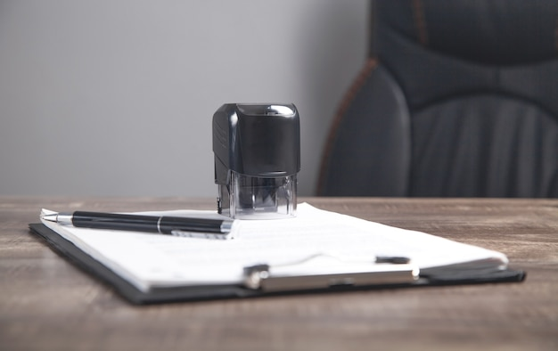 Document, pen en stempel op tafel.