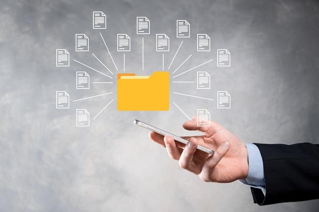 Documentbeheersysteem dms. zakenman houdt map- en documentpictogram vast. software voor het archiveren, zoeken en beheren van bedrijfsbestanden en informatie. internettechnologieconcept. digitale beveiliging.