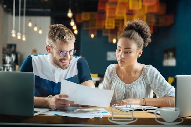 Documenten bekijken. hardwerkende jonge knappe freelancers die het druk hebben terwijl ze naar documenten kijken