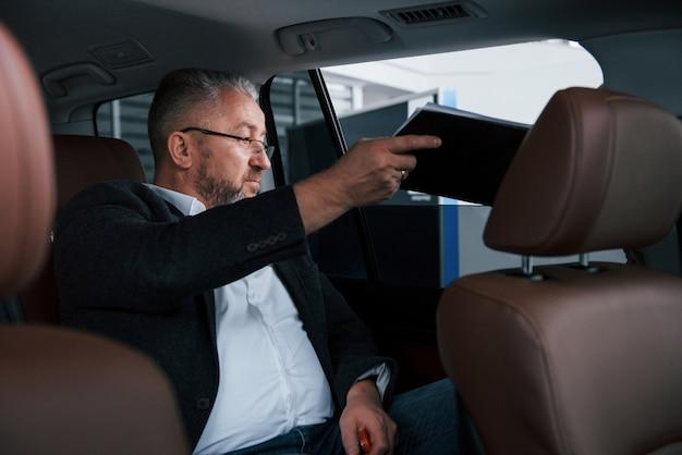 Documenten door het open raam. papierwerk op de achterbank van de auto. senior zakenman met documenten