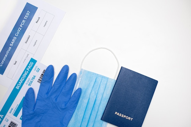 Documenten en items voor vliegreizen tijdens de covid-19-epidemie: paspoort, ticket, pcr-test voor covid-19, gezichtsmasker, handschoenen, kopieerruimte.