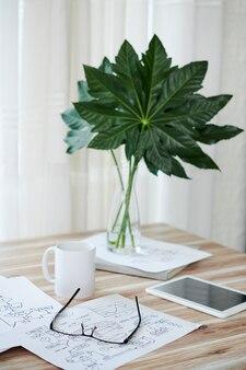 Documenten met blokschema's, koffie en tabletcomputer op tafel versierd met bladeren in vaas
