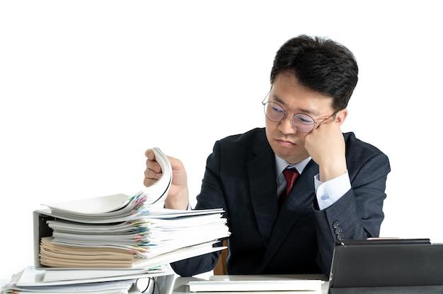Documenten of rapporten gestapeld met aziatische mannelijke zakenman van middelbare leeftijd.