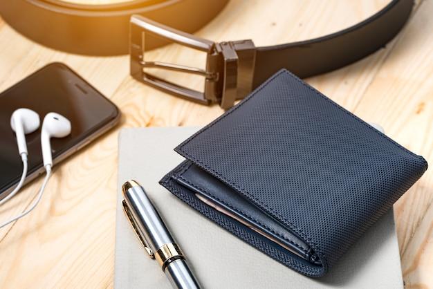 Documenten, pen, riem en een lederen portefeuille op een houten bureau.