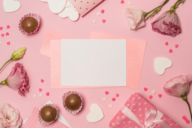 Documenten tussen bloemen dichtbij huidige doos en chocoladesuikergoed