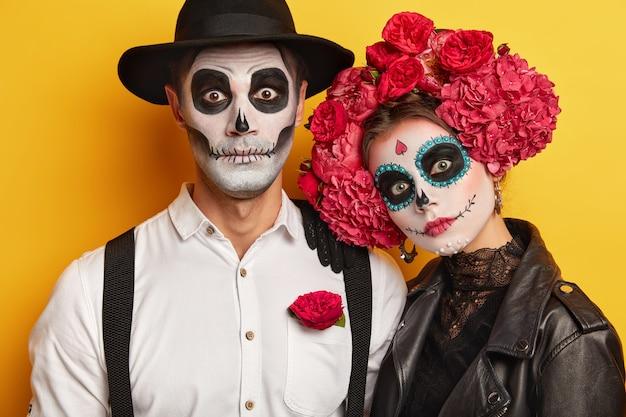 Dode vrouw en man dragen schedelmake-up, geschilderd voor halloween, kijken verrassend naar de camera, gekleed in zwart-witte outfit voor allerheiligen, geïsoleerd op gele achtergrond.