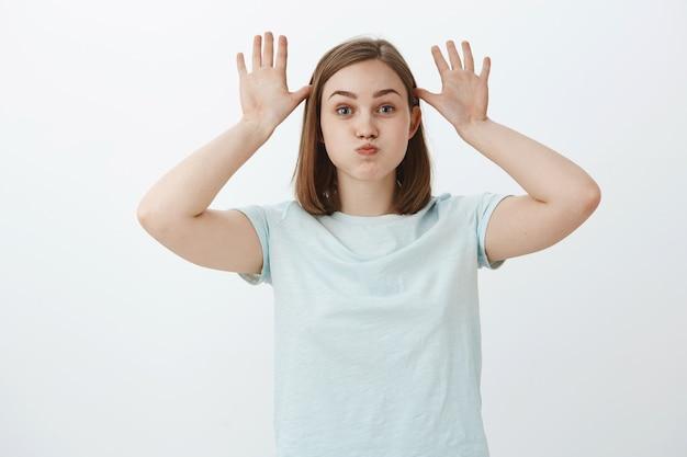 Doe alsof je nog een kind bent. portret van leuk grappig en speels volwassen meisje in t-shirt aping gezichten maken, adem inhouden en pounting terwijl handpalmen in de buurt van hoofd spelen met kinderen over witte muur