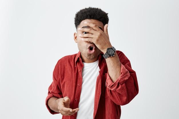 Doe dat niet. kopieer ruimte. het portret van een jonge man met een zwarte huid en een afrokapsel in een wit t-shirt en een rood hemd met zijn hand dicht, kan niet kijken naar zijn vriend die stomme dingen doet.