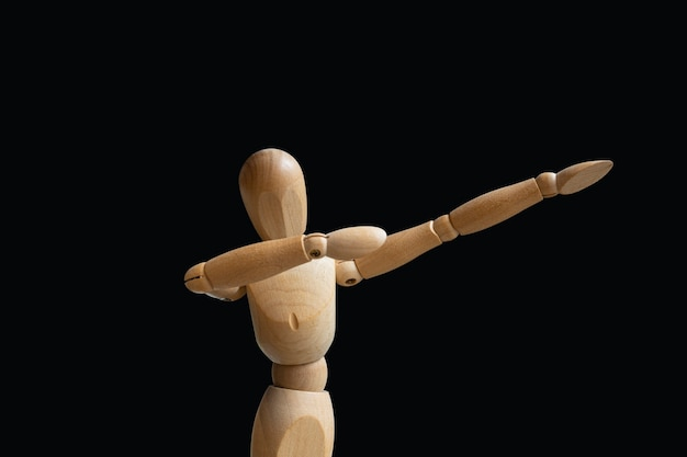 Doe de dab. houten marionet op zwarte achtergrond. geïsoleerde afbeelding