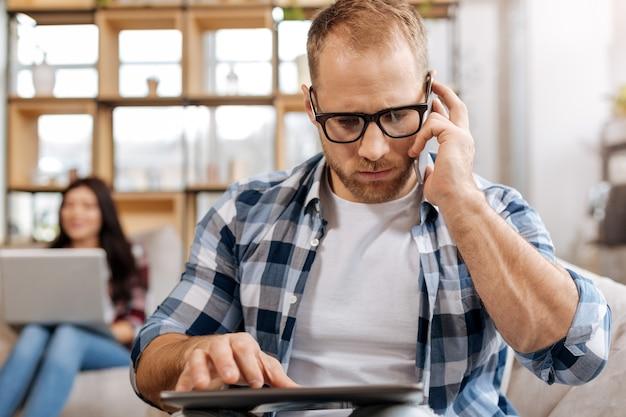 Doe een beroep op zaken. ernstige zelfverzekerde zelfstandige man die een mobiele telefoon vasthoudt en belt tijdens het werken op de tablet