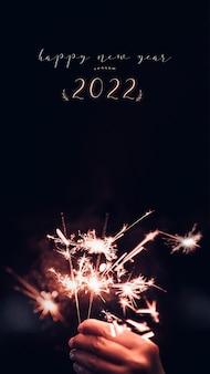 Doe een wens nieuwjaar 2022 met hand met brandende sparkler vuurwerk ontploffing met op een zwarte bokeh achtergrond 's nachts, vakantie feest evenement party.vertical ratio
