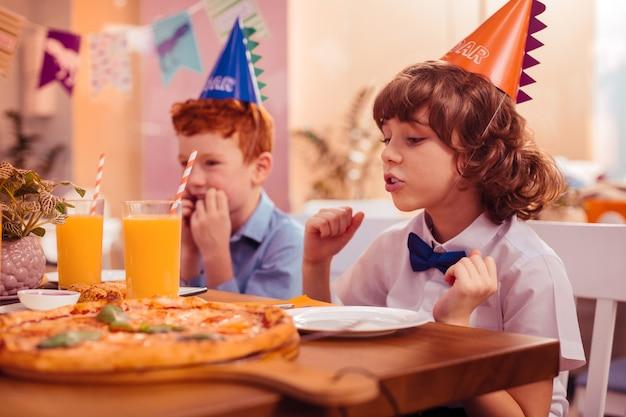 Doe een wens. opgetogen kind met krullend haar dat een papieren hoed draagt en een feestelijk diner verwacht