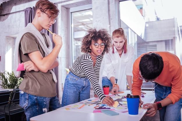 Doe het samen. vrolijke donkere huid meisje permanent in de buurt van haar vrienden tijdens het voltooien van de taak
