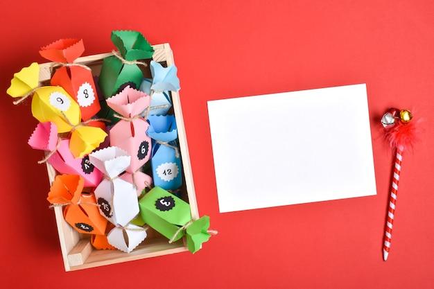 Doe het zelf. adventskalenders gemaakt van gekleurd papier in de vorm van snoep in een houten kist op een rode achtergrond. een blanco vel papier voor de opdracht aan de adventskalender.
