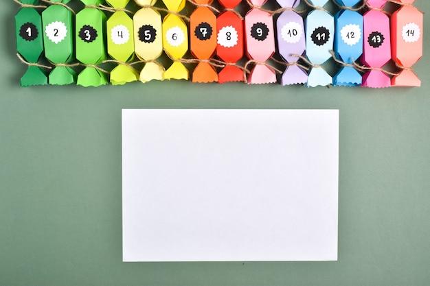 Doe het zelf. adventskalenders van gekleurd papier in de vorm van snoepjes. stap-voor-stap gedetailleerde instructies. nieuwjaars ambacht.