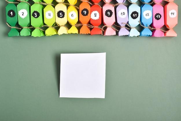 Doe het zelf. adventskalenders van gekleurd papier in de vorm van snoepjes. stapsgewijze instructies. stap 4. het vierkant is klaar.