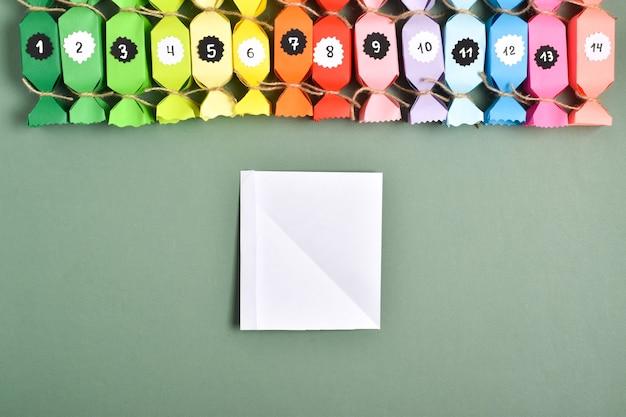 Doe het zelf. adventskalenders van gekleurd papier in de vorm van snoepjes. stapsgewijze instructies. stap 5. buig een kleine strook om verder te lijmen.