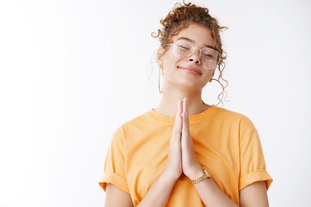 Doe me alsjeblieft een plezier. portret charmant vriendelijk schattig gelukkig blanke roodharige jong meisje sproeten sluiten ogen opgelucht ontspannen pers handpalmen samen bidden gebaar smeken om gunst, hoop hebben gelukkige dag