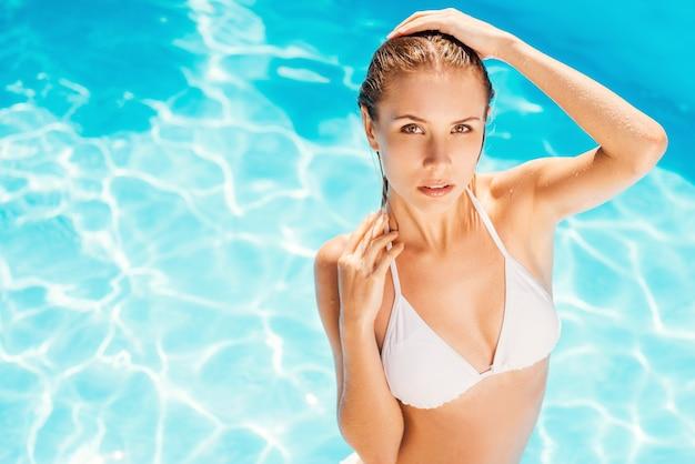 Doe mee in het zwembad! bovenaanzicht van aantrekkelijke jonge vrouw in witte bikini die bij het zwembad staat en naar de camera kijkt