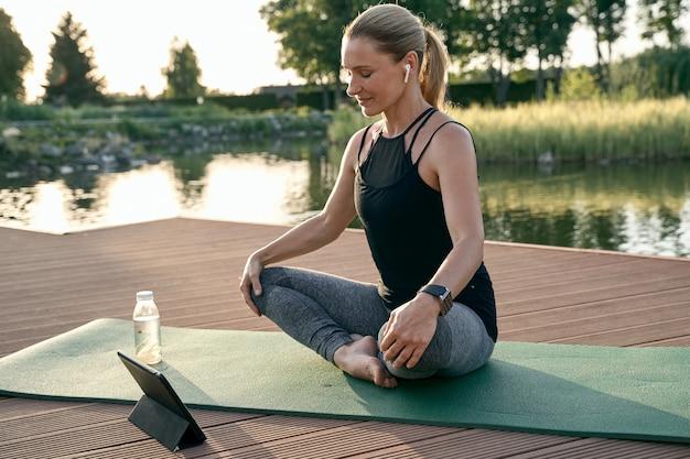 Doe mee met de wereld van yoga, sportieve mooie vrouw die mediteert met een tablet-pc terwijl ze yoga doet op een mat