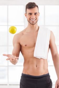 Doe mee met een gezonde levensstijl! knappe jonge gespierde man met handdoek op schouder die een appel overgeeft en naar de camera glimlacht
