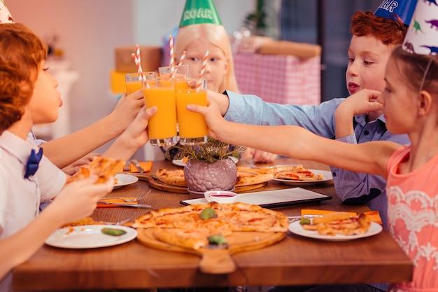 Doe met ons mee. emotionele jongen die pizza in de linkerhand houdt terwijl hij met zijn vrienden praat